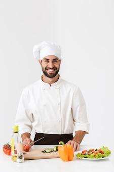 Chefe bonito de uniforme sorrindo e cozinhando salada de legumes na tábua de madeira isolada sobre a parede branca