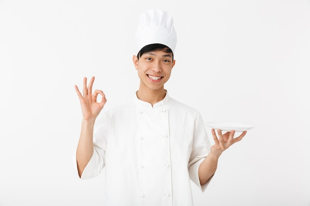 Chefe cândido asiático com uniforme branco de cozinheiro, sorrindo para a câmera, segurando um prato isolado na parede branca