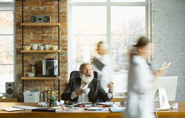 Chefe cansado descansando em seu local de trabalho enquanto pessoas ocupadas se movendo perto turva. trabalhador de escritório, gerente trabalhando, bebendo café e dando instruções para seus colegas. negócios, trabalho, conceito de carga de trabalho.
