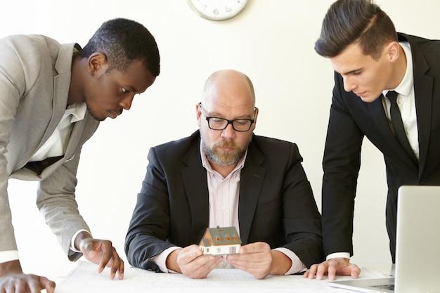Chefe caucasiano em copos segurando a casa modelo em escala do futuro imobiliário enquanto dois jovens arquitetos apresentando o projeto de construção para ele.