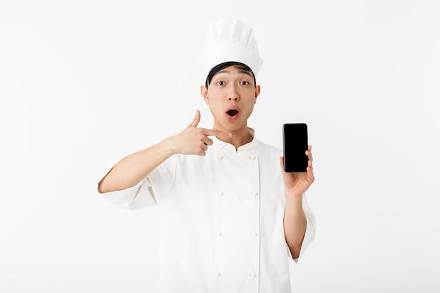 Chefe chinês animado com uniforme branco de cozinheiro e chapéu de chef segurando um telefone celular isolado sobre uma parede branca