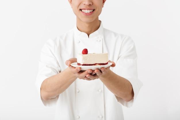Chefe chinês animado com uniforme de cozinheiro branco, sorrindo para a câmera enquanto segura o prato com o saboroso cheesecake isolado na parede branca