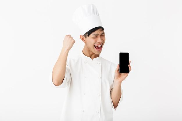 Chefe chinês bonito com uniforme branco de cozinheiro e chapéu de chef segurando o telefone celular isolado sobre a parede branca