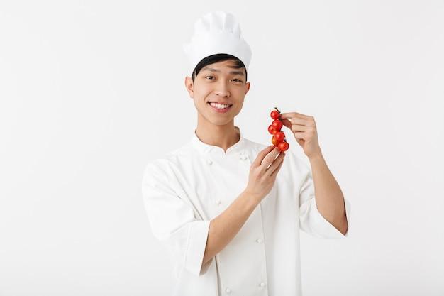 Chefe chinês positivo com uniforme de cozinheiro branco, sorrindo para a câmera, segurando vegetais de tomate isolados sobre a parede branca