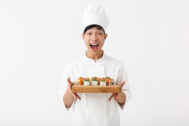 Chefe chinês profissional com uniforme de cozinheiro branco, sorrindo para a câmera enquanto segura o prato com o conjunto de sushi isolado na parede branca