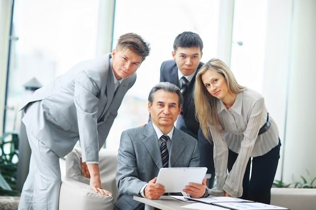 Chefe com tablet digital e sua equipe de negócios em um escritório moderno