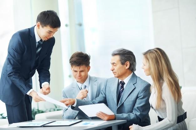 Chefe com tablet digital e sua equipe de negócios