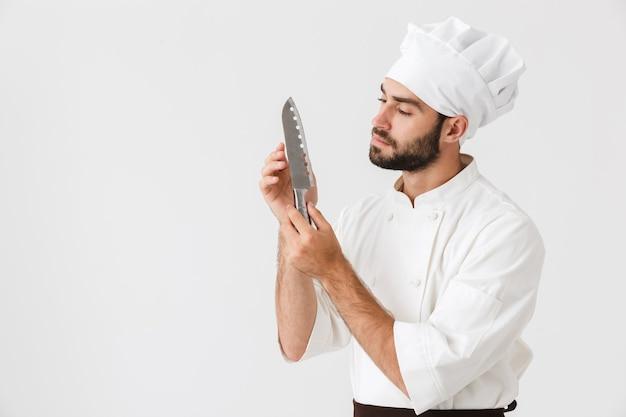 Chefe concentrado em uniforme de cozinheiro segurando uma grande faca de metal afiada isolada sobre uma parede branca