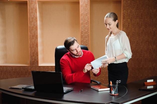 Chefe confiante com papel explicando algo à secretária