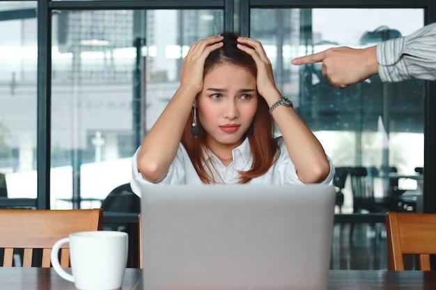 Chefe da mão, apontando ansioso deprimido mulher de negócios asiáticos