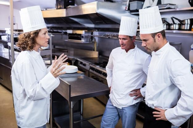 Chefe de cozinha chateado conversando com sua equipe