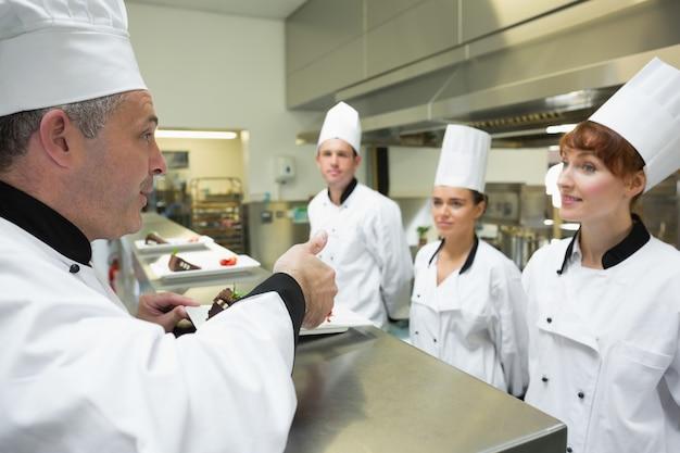 Chefe de cozinha classifica a placa de um de seus aprendizes