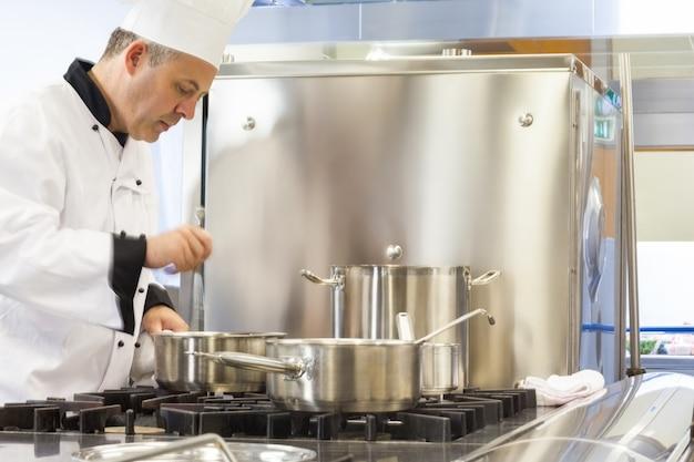 Chefe de cozinha concentrado mexendo na panela