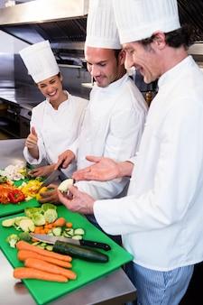 Chefe de cozinha ensinando seus colegas a cortar legumes