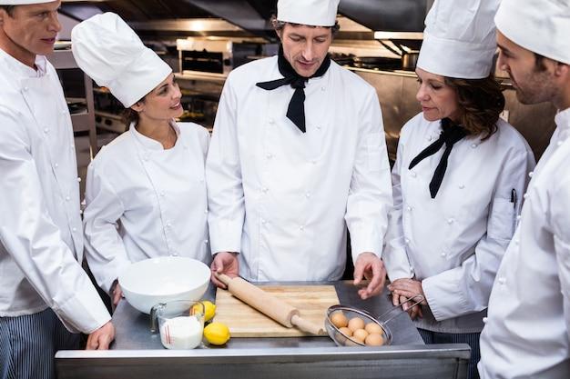 Chefe de cozinha ensinando sua equipe a preparar uma massa