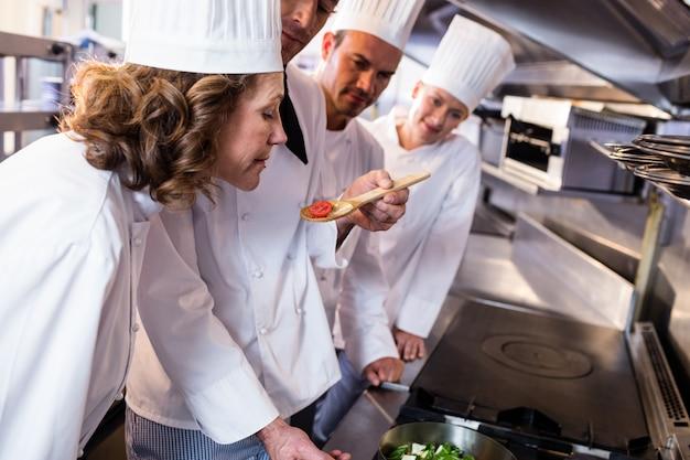 Chefe de cozinha mostrando comida para seus colegas