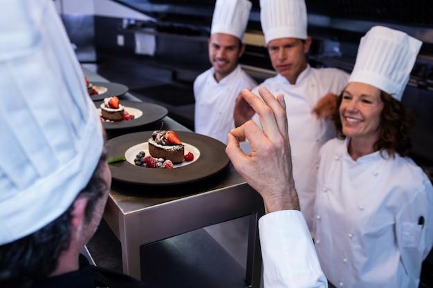 Chefe de cozinha mostrando sinal de mão ok depois de inspecionar pratos de sobremesa