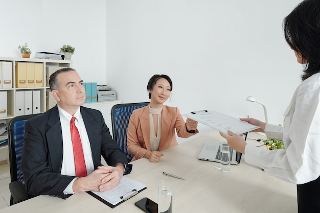 Chefe de departamento e gerente de rh pedindo ao candidato para preencher o formulário cv antes da entrevista
