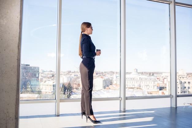 Chefe de mulher de negócios confiante em um escritório moderno ou janela de hotel, apreciando a vista da cidade grande, mulher líder, empresário, pensando no sucesso futuro, planejando novas oportunidades,