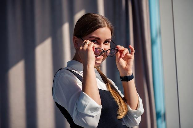 Chefe de mulher de negócios confiante em um escritório moderno usando óculos, líder feminina, proprietária de empresa, pensando no sucesso futuro, planejando novas oportunidades