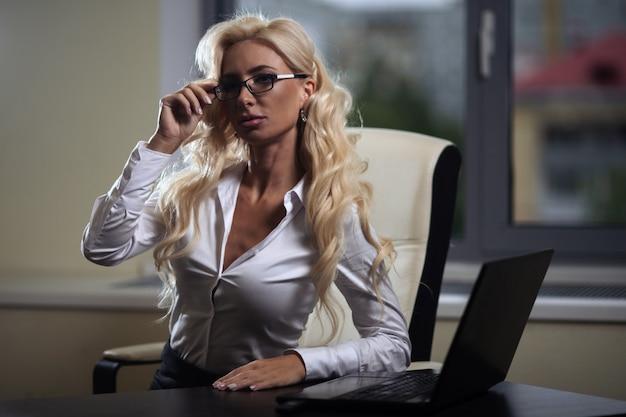 Chefe de mulher sentada em uma mesa no escritório