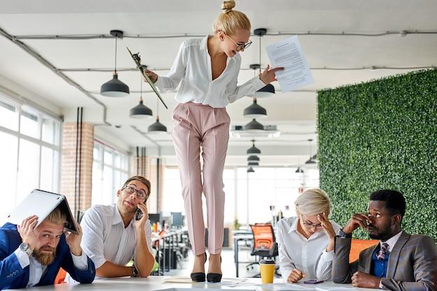 Chefe de mulher zangada criticando funcionários frustrados no local de trabalho do escritório