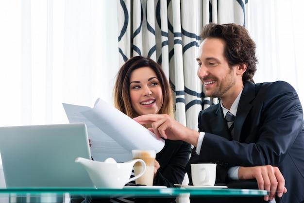 Chefe e assistente ou no hotel trabalhando juntos