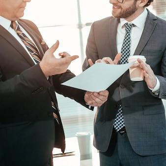 Chefe e funcionário discutindo um documento de trabalho