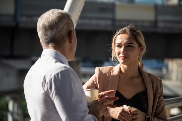 Chefe e mulher de negócios fala e bebe café