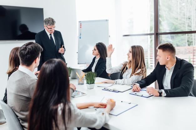 Chefe empresário segurando as mãos de papéis e sorrindo. jovem equipe de colegas de trabalho fazendo uma grande discussão de negócios no moderno escritório de coworking.