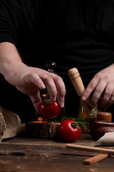 Chefe está preparando tomate na mesa