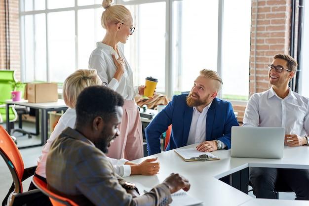 Chefe executiva agradável e bonita discutindo ideias de negócios com os funcionários