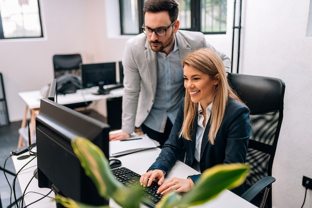 Chefe executivo masculino que supervisiona o trabalho do computador do empregado do sexo feminino novo.