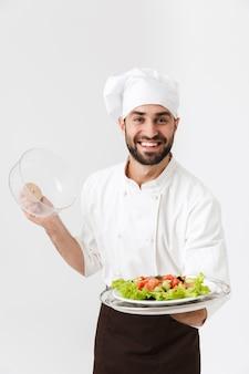 Chefe feliz com uniforme de cozinheiro, sorrindo e segurando o prato com salada de legumes isolada na parede branca
