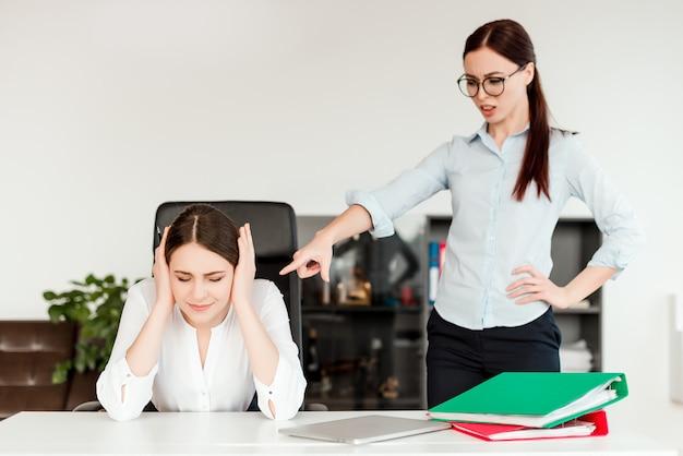 Chefe feminino dando ordens para o empregado no escritório