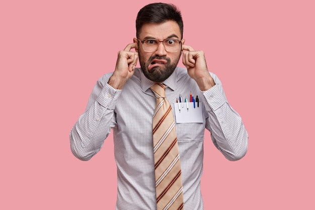 Chefe masculino irritado e insatisfeito vestido formalmente, tapa os ouvidos, não quer ouvir reclamações dos colegas, franze a testa em desgosto