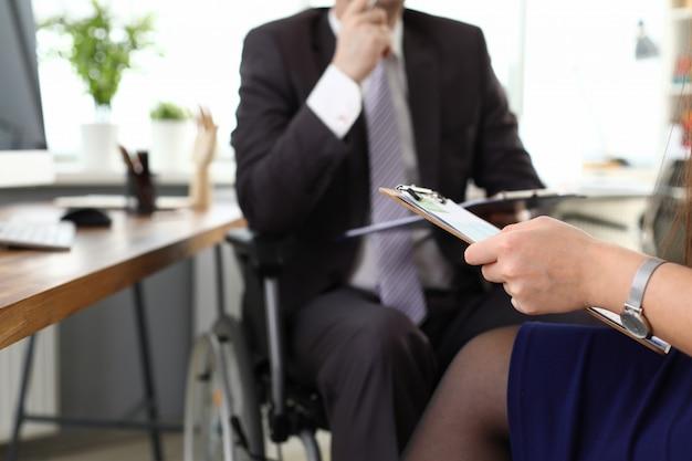 Chefe masculino na cadeira de rodas fala com o escritório da mulher