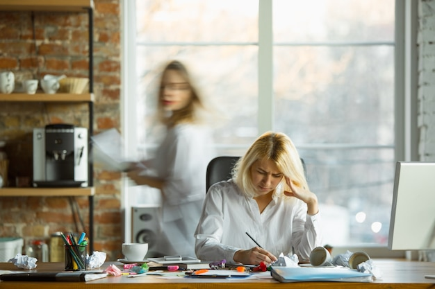 Chefe nervosa e cansada em seu local de trabalho, ocupada enquanto as pessoas se moviam perto do borrão. trabalhadora de escritório, gerente de trabalho, tem problemas e prazos, seus colegas distraem. negócios, trabalho, conceito de carga de trabalho.
