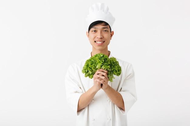 Chefe otimista asiático com uniforme branco de cozinheiro, sorrindo para a câmera enquanto segura uma salada de alface verde isolada na parede branca