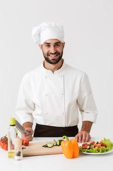 Chefe profissional de uniforme, sorrindo e cozinhando salada de legumes na tábua de madeira isolada sobre a parede branca