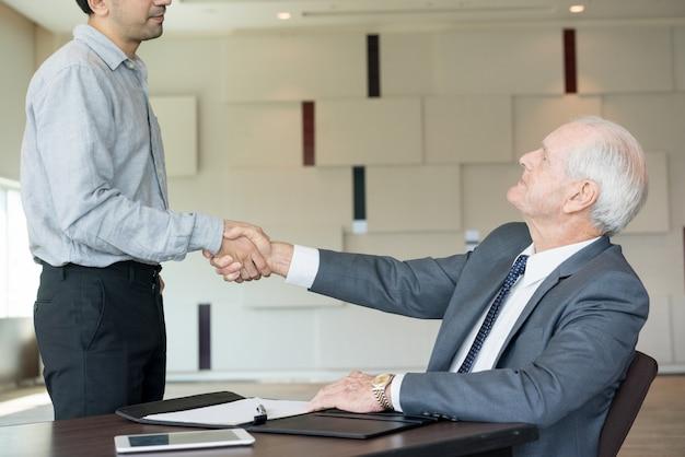 Chefe respeitável fazendo handshake com empregado