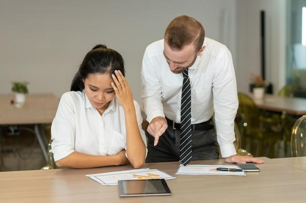 Chefe zangado, apontando para o relatório enquanto repreendendo empregado asiático