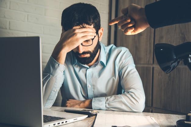Chefe zangado com trabalhador triste na mesa