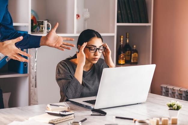 Chefe zangado e mulher na mesa do escritório