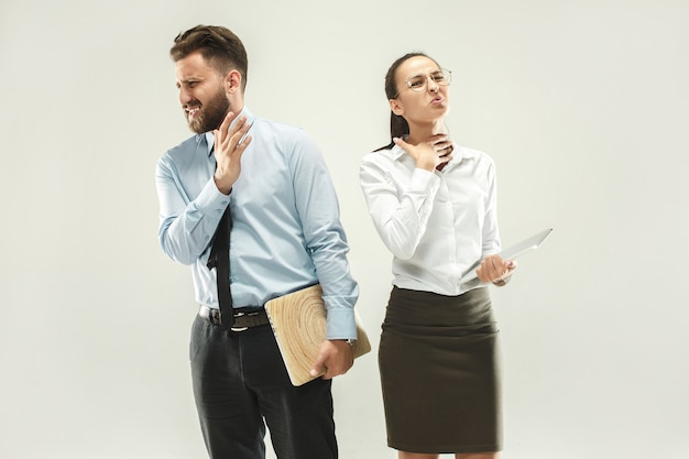 Chefe zangado. homem e sua secretária permanente no escritório ou estúdio.
