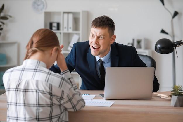 Chefe zangado repreendendo a secretária no escritório