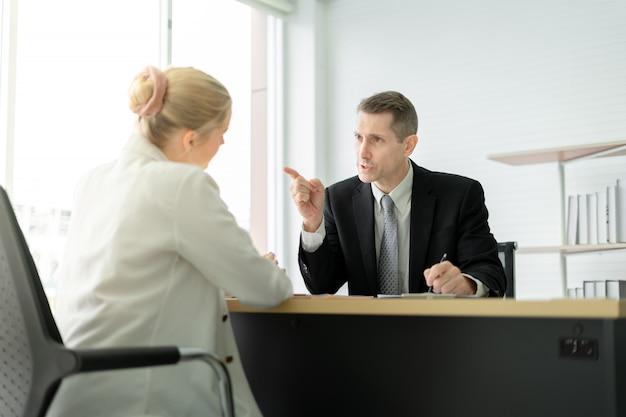 Chefe zangado repreendendo e apontando o dedo no rosto de empregado de mulher na sala de reuniões no escritório