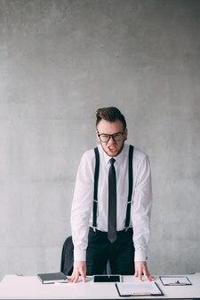 Chefe zangado. retrato de homem de negócios jovem furioso, em pé na mesa, gritando. copie o espaço.