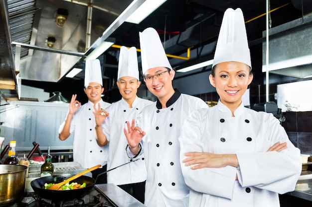 Chefs asiáticos na cozinha do restaurante do hotel
