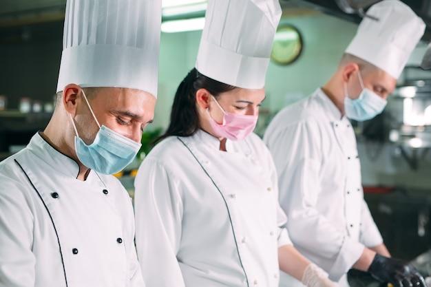 Chefs com máscaras protetoras e luvas preparam os alimentos na cozinha de um restaurante ou hotel.